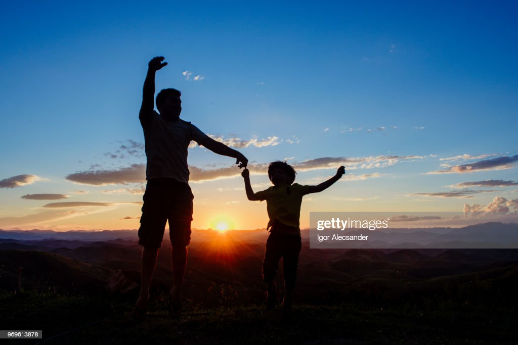 Father and son having fun at sunset : Stock Photo