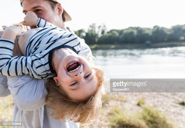 father and son having fun at the riverside - outdoors stock-fotos und bilder