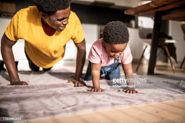 father and son having fun doing push-ups - son stock pictures, royalty-free photos & images