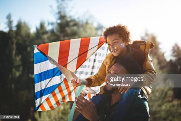 vader en zoon plezier vliegende kite op zonnige dag - vlieger stockfoto's en -beelden