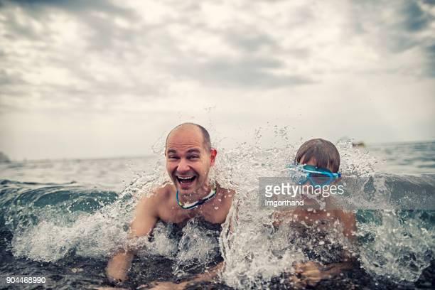 Padre e hijo divirtiéndose en el mar frío
