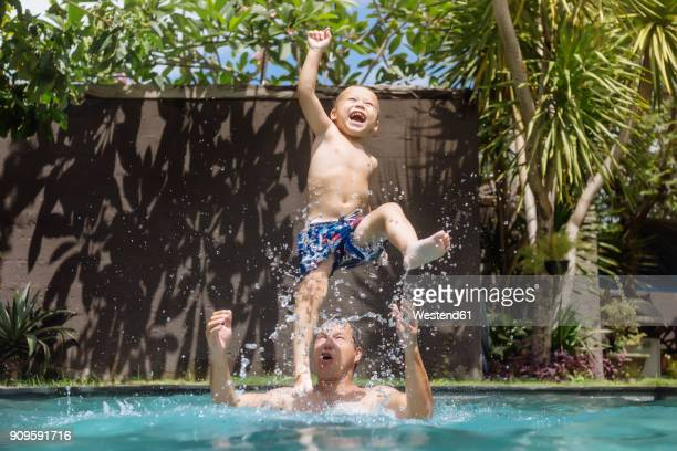 Father and son having fun in swimming pool