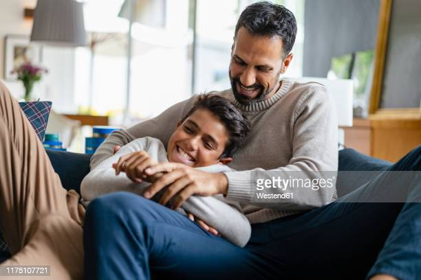 father and son having fun on couch in living room - pre adolescent child stock pictures, royalty-free photos & images