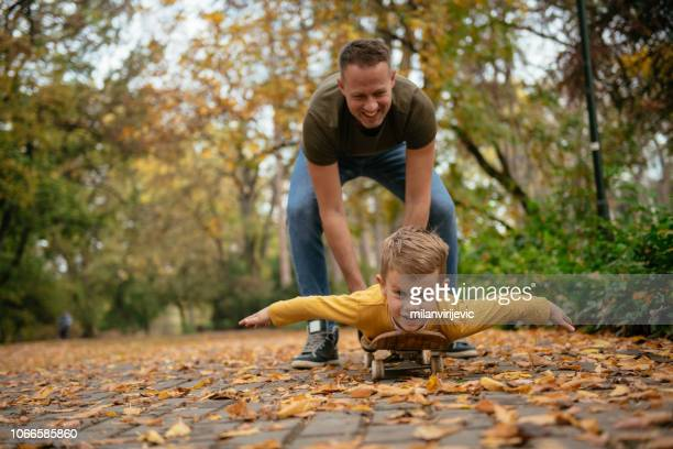 father and son having fun on skateboard - fathers day stock pictures, royalty-free photos & images