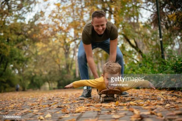 father and son having fun on skateboard - dia dos pais imagens e fotografias de stock