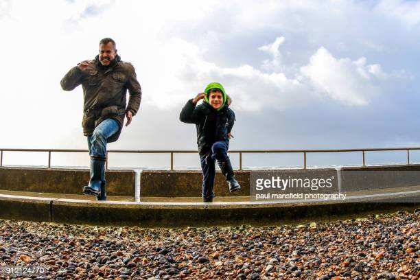 Father and son having fun on stormy coastal path