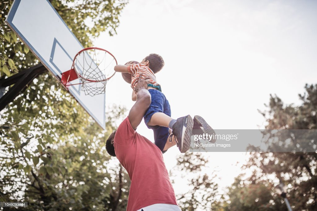 Father and son having fun, playing basketball outdoors : Stock Photo