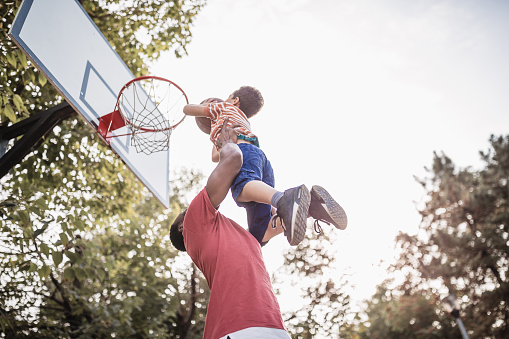 Father and son having fun, playing basketball outdoors 1049293884