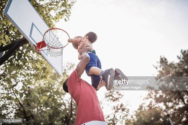 father and son having fun, playing basketball outdoors - termine sportivo foto e immagini stock