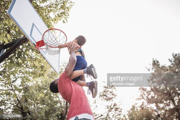father and son having fun, playing basketball outdoors - shooting baskets stock photos and pictures