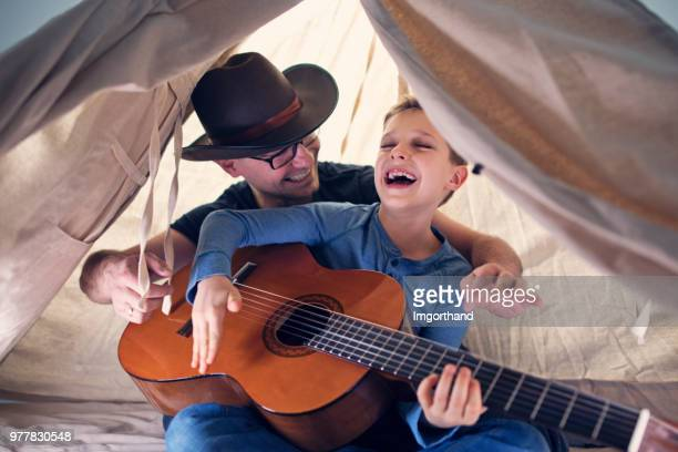 father and son having fun playing guitar in teepee tent - imgorthand stock photos and pictures