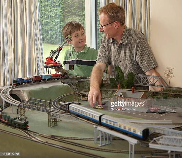 father and son having fun playing with a train set