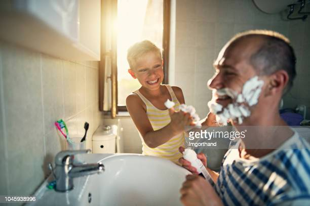 father and son having fun shaving - shaving stock pictures, royalty-free photos & images
