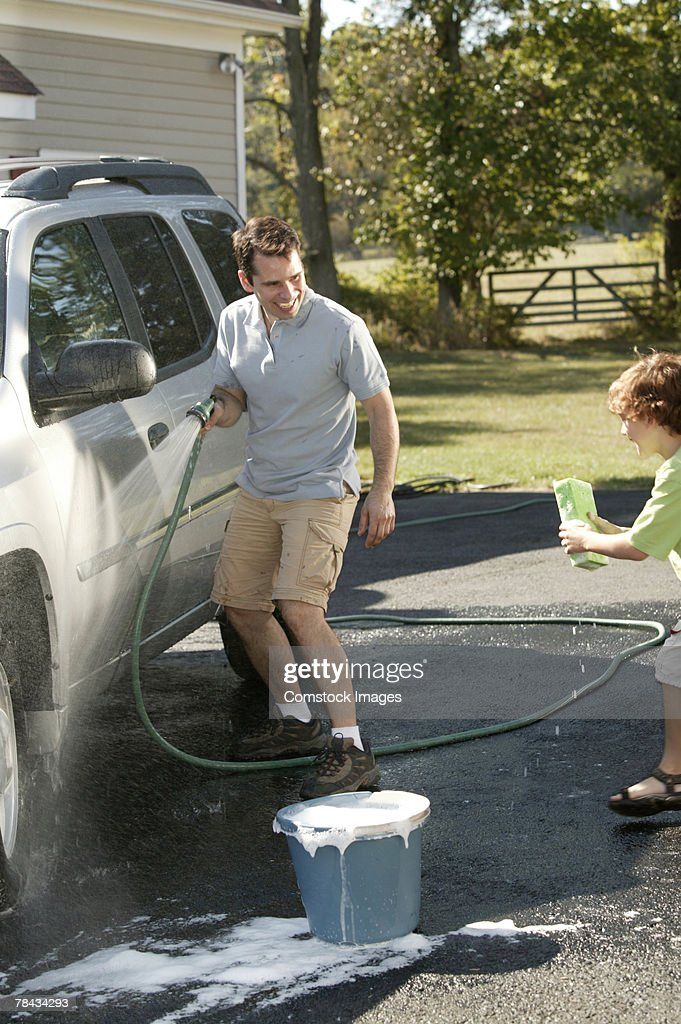 Father and son having fun washing car : Stockfoto