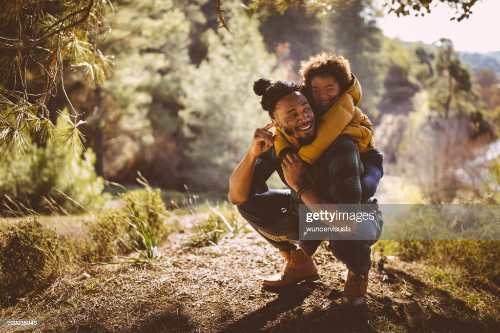 Father and son having fun with piggyback ride in forest : Stock Photo