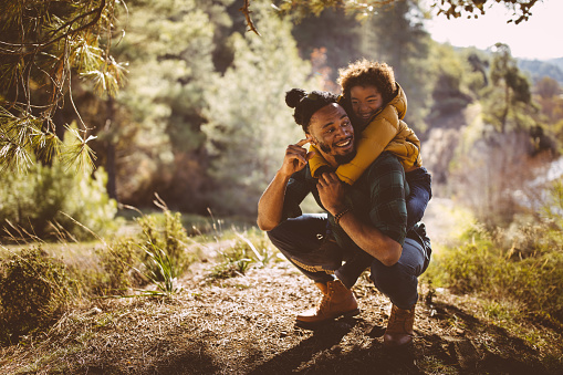 Father and son having fun with piggyback ride in forest 920038046