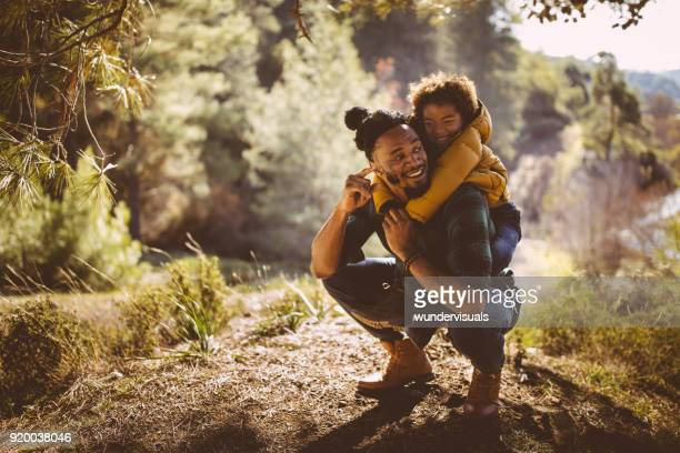 father and son having fun with piggyback ride in forest - woodland stock pictures, royalty-free photos & images