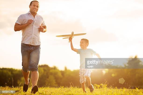 Pai e filho a divertir-se com o avião de brinquedo ao ar livre.