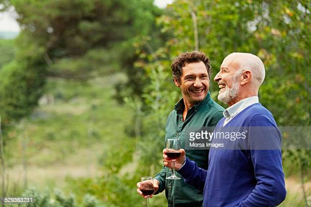 father and son having red wine in park - sohn stock-fotos und bilder