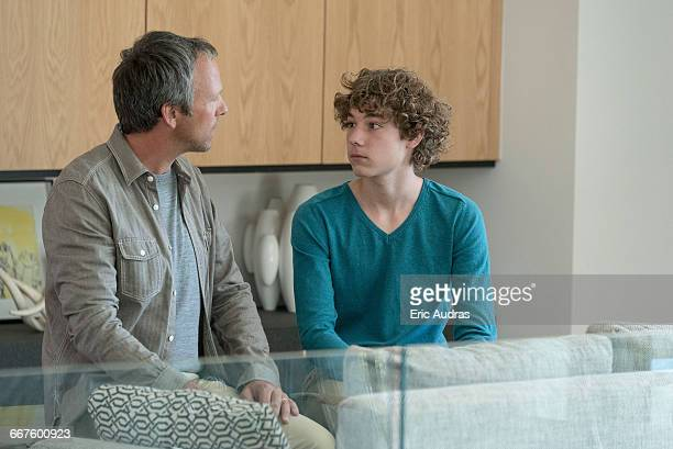 Father and son having serious discussion in a living room