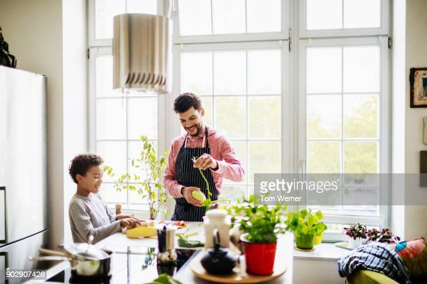 father and son helping each other prepare salad for lunch - family with one child stock pictures, royalty-free photos & images