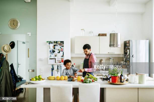 father and son helping each other prepare some lunch - north african ethnicity stock pictures, royalty-free photos & images