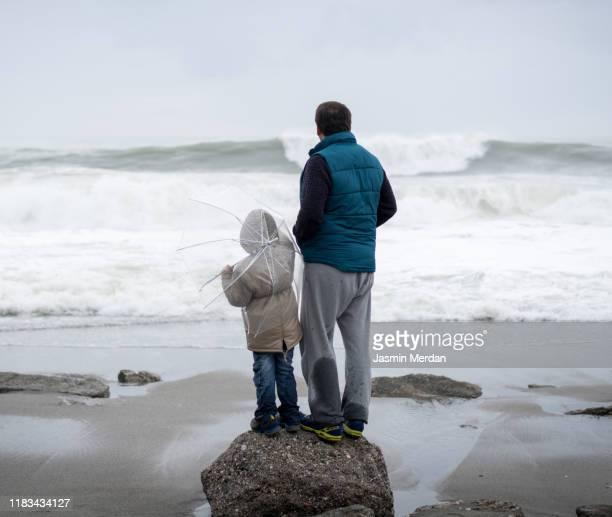 father and son hike near sea - jasmin sturm stock-fotos und bilder