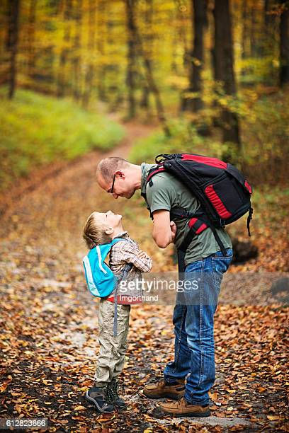Father and son hiking in autumn beech forest