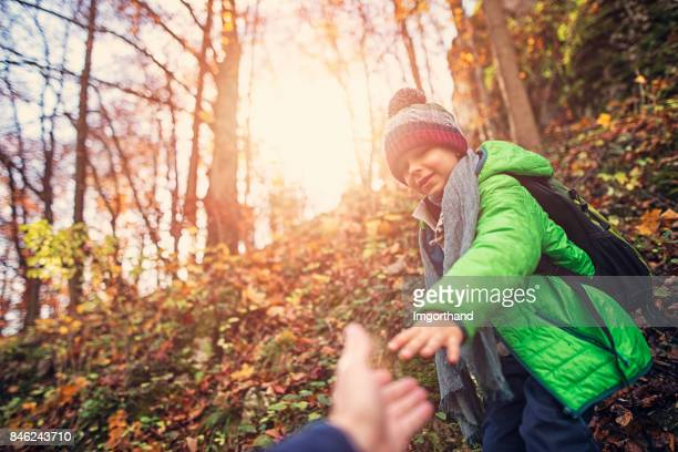 Father and son hiking in autumn forest