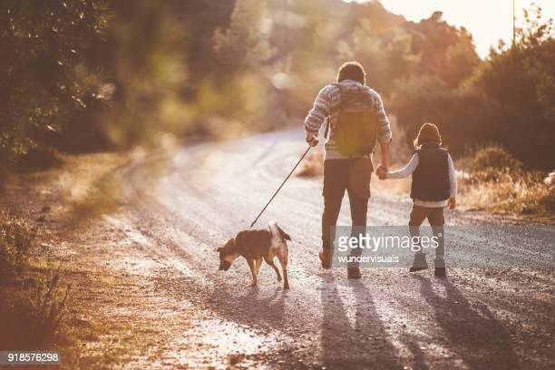 father and son hiking on mountain footpath with family dog - dirt track stock pictures, royalty-free photos & images