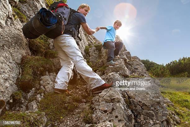 father and son hiking on rocky terrain - freizeitaktivität im freien stock-fotos und bilder