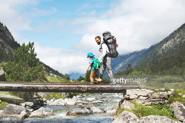 father and son hiking together in mountains - mood stream stock pictures, royalty-free photos & images