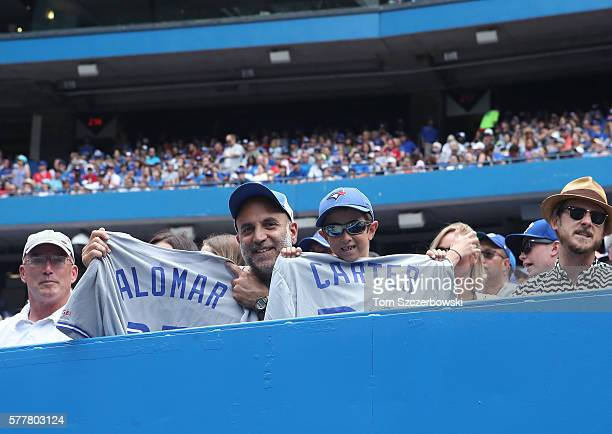 A father and son hold up their jerseys of former players Roberto Alomar of the Toronto Blue Jays and Joe Carter during MLB game action against the...