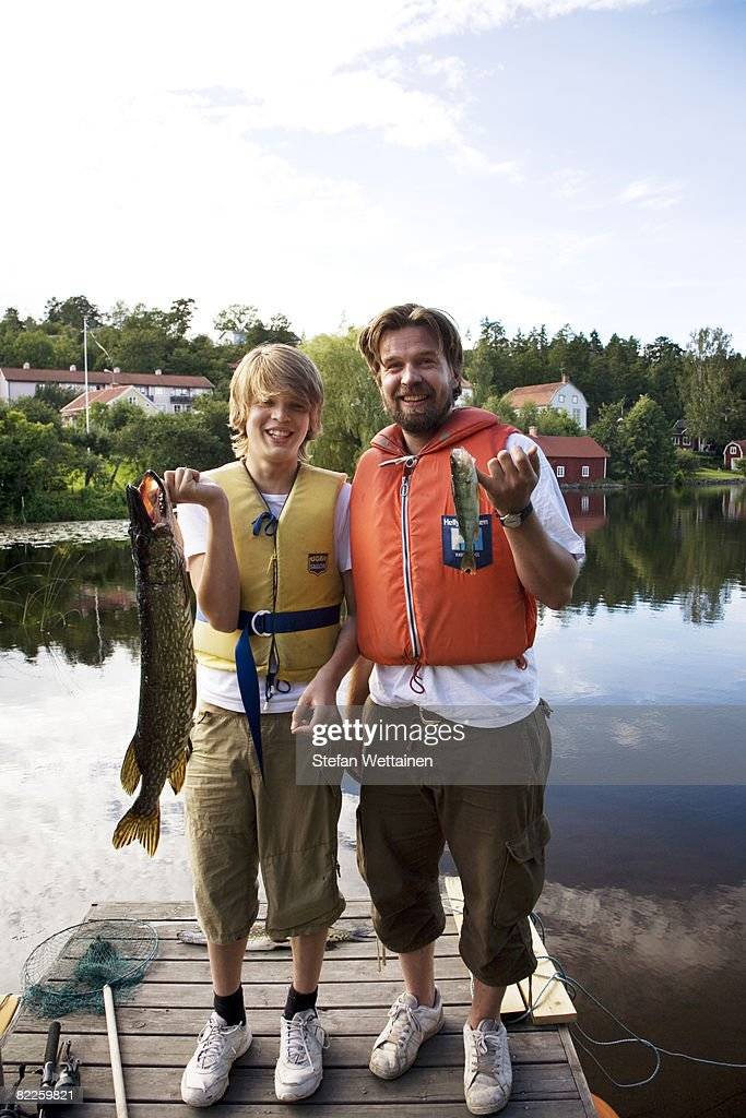 Father and son holding fishes standing on a jetty Sweden. : Stock Photo