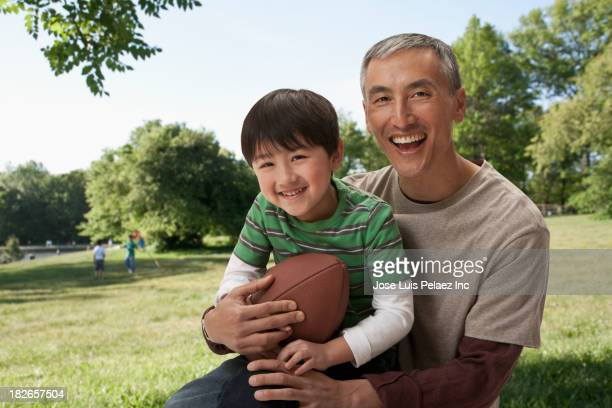 Father and son holding football in park