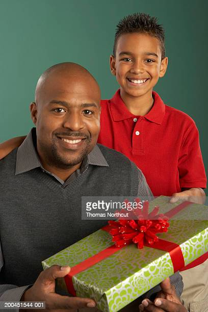 Father and son (10-12) holding gift, smiling, portrait