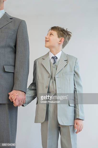 Father and son holding hands against white background