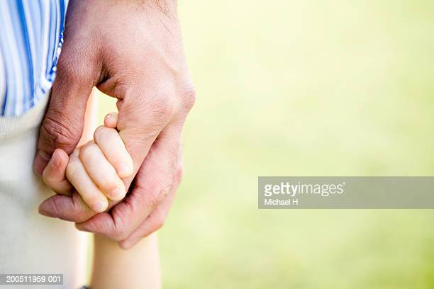 Father and son (2-4) holding hands, close-up of hands