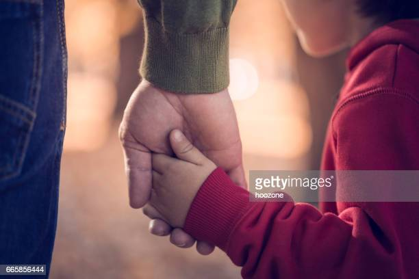 father and son holding hands in park - father stock pictures, royalty-free photos & images