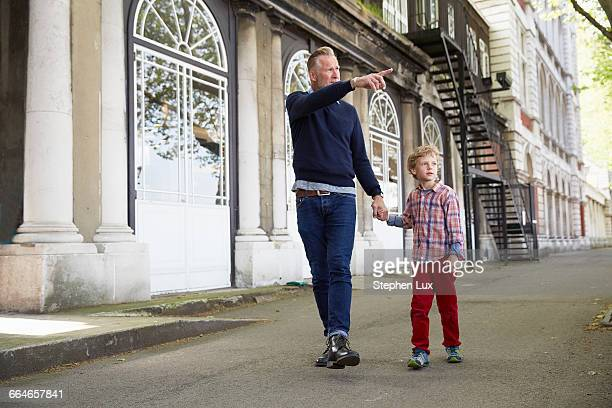 Father and son holding hands in street