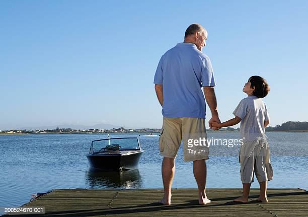 father and son (6-8) holding hands on jetty, rear view - vertäut stock-fotos und bilder