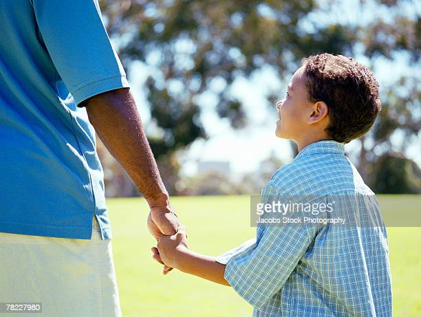 father and son holding hands - side by side stock pictures, royalty-free photos & images