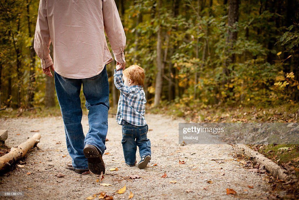Father and Son Holding Hands While Walking through Autumn Woods : Stock Photo