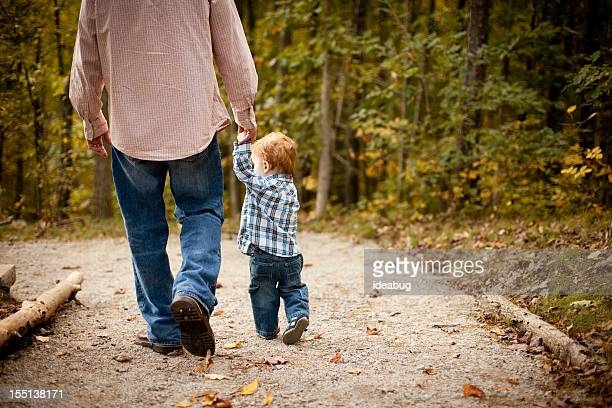 Father and Son Holding Hands While Walking through Autumn Woods