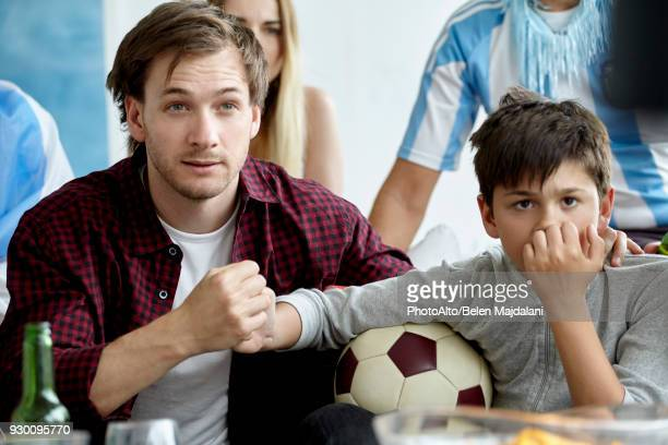 Father and son holding hands while watching football match at home