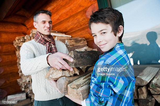 Father and son holding logs