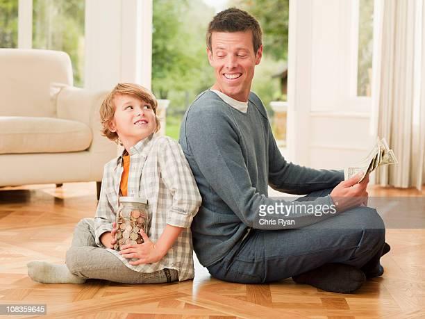 Vater und Sohn holding Geld sitzen Rücken an Rücken