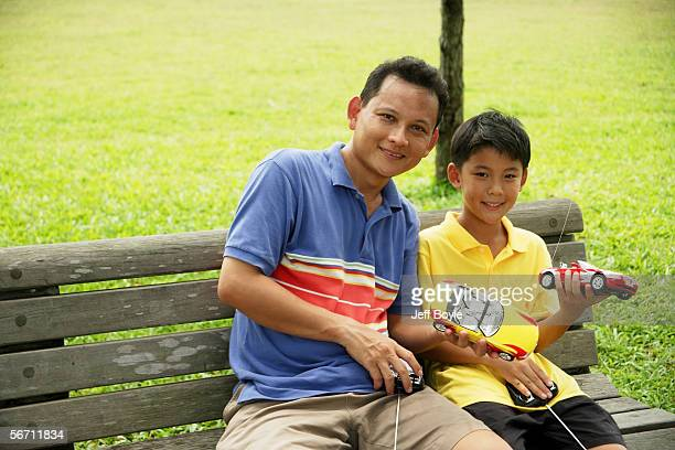 father and son holding remote control cars, smiling - remote control car games stock pictures, royalty-free photos & images