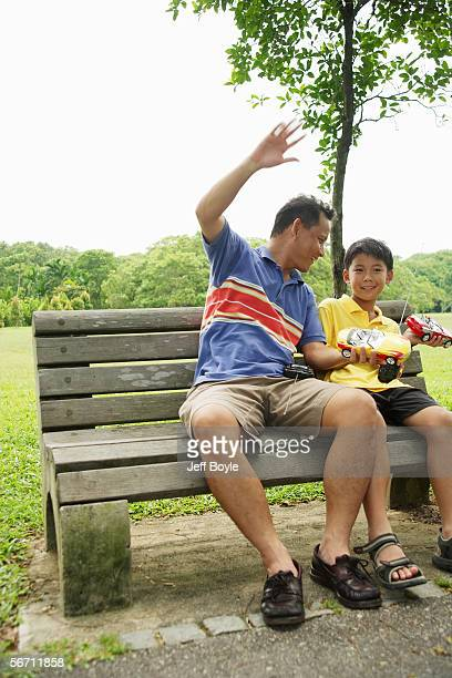 father and son holding remote control cars, smiling - remote control car games stock photos and pictures