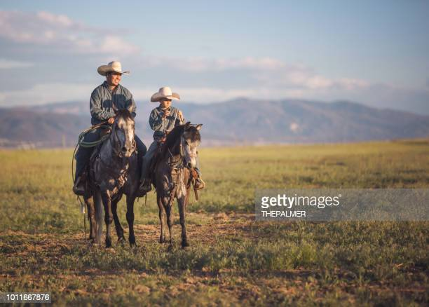 father and son horseback riding - ranch stock pictures, royalty-free photos & images